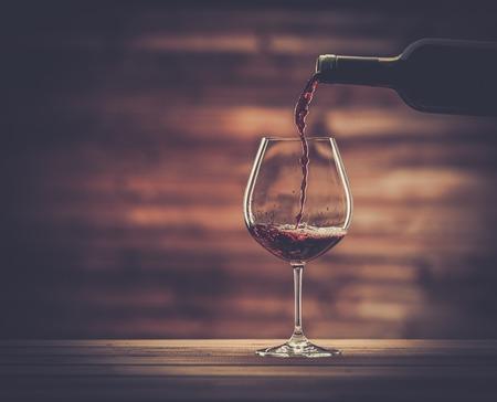 Photo pour Pouring red wine into the glass against wooden background - image libre de droit