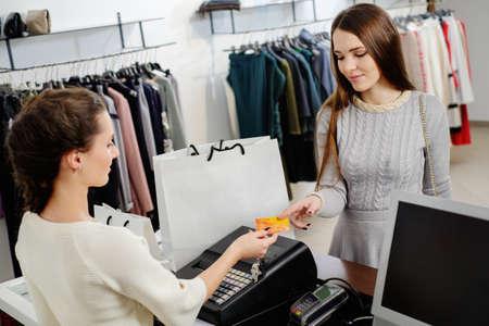Foto de Happy woman customer paying with credit card in fashion showroom - Imagen libre de derechos