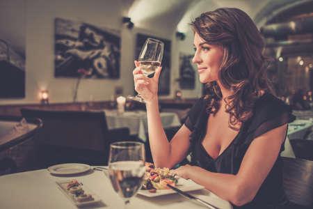 Foto de Beautiful young lady alone in restaurant - Imagen libre de derechos