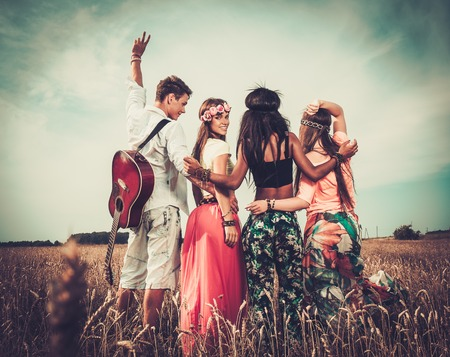Photo for Multi-ethnic hippie friends with guitar in a wheat field - Royalty Free Image