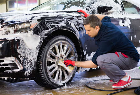 Foto de Man worker washing car's alloy wheels on a car wash - Imagen libre de derechos