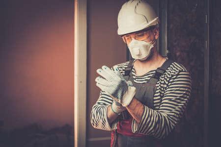 Foto de Builder in protective wear during new building construction - Imagen libre de derechos