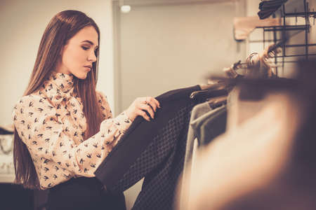 Photo for Young woman choosing clothes on a rack in a showroom - Royalty Free Image