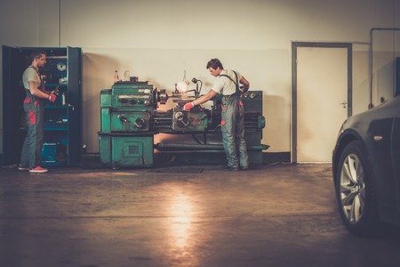 Photo for Serviceman working on turning lathe in car workshop - Royalty Free Image