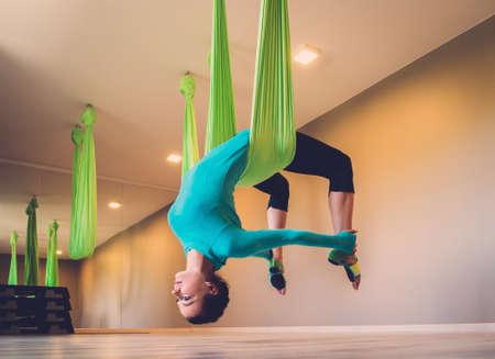 Foto de Young woman performing antigravity yoga exercise - Imagen libre de derechos