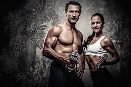 Foto de Athletic man and woman with a dumbbells - Imagen libre de derechos