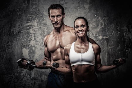 Photo pour Athletic man and woman with a dumbbells - image libre de droit