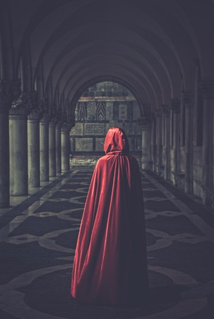 Photo for Woman in red cloak walking away - Royalty Free Image