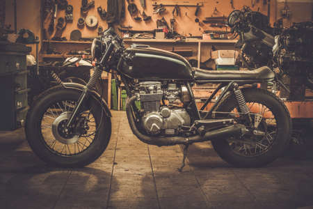 Photo pour Vintage style cafe-racer motorcycle in customs garage - image libre de droit