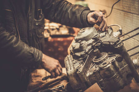 Photo pour Mechanic working with with motorcycle engine in a workshop - image libre de droit
