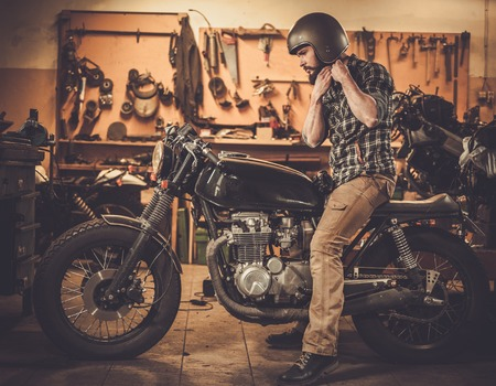 Foto de Rider and his vintage style cafe-racer motorcycle in customs garage - Imagen libre de derechos
