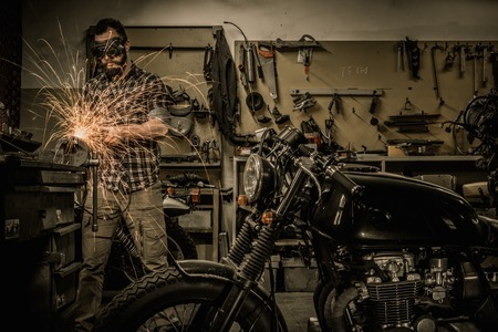 Photo for Mechanic doing lathe works in motorcycle customs garage - Royalty Free Image