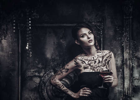 Photo pour Tattooed beautiful woman in old spooky interior - image libre de droit