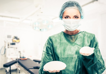 Photo pour Plastic surgeon woman holding different size silicon breast implants in surgery room interior - image libre de droit
