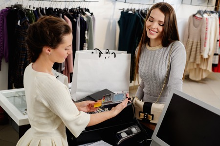 Photo for Happy woman customer paying with credit card in fashion showroom - Royalty Free Image