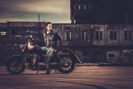Foto de Biker and his bobber style motorcycle on a city streets - Imagen libre de derechos