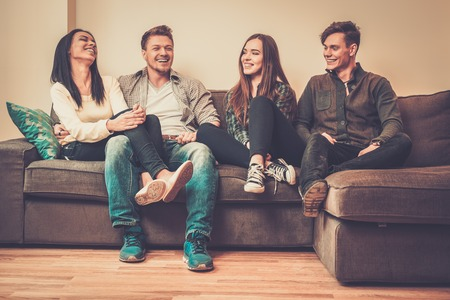 Photo pour Cheerful multi-ethnic friends sitting on a sofa - image libre de droit