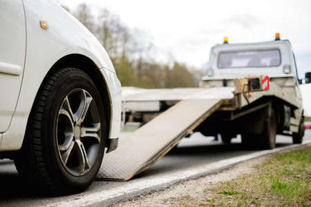Foto de Loading broken car on a tow truck on a roadside - Imagen libre de derechos
