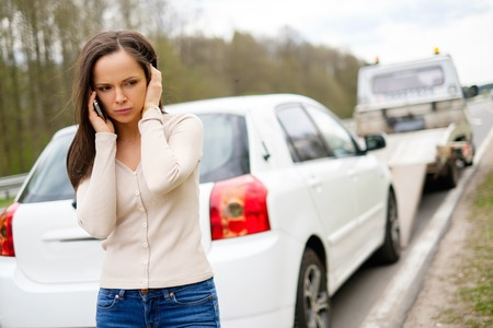 Foto de Woman calling while tow truck picking up her car - Imagen libre de derechos