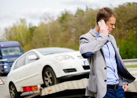 Foto de Man calling while tow truck picking up his broken car - Imagen libre de derechos