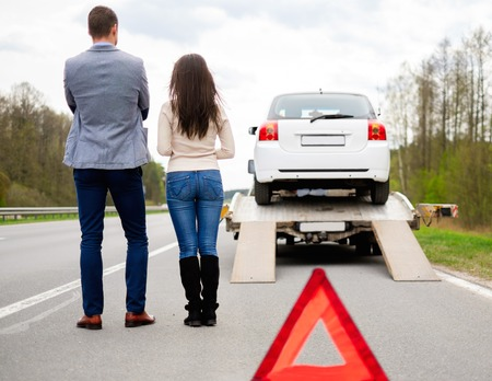 Foto de Couple near tow-truck picking up broken car - Imagen libre de derechos