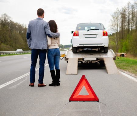 Foto de Couple near tow-truck picking up broken car - Imagen libre de derechos