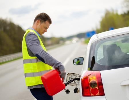 Foto de Man refuelling her car on a highway roadside - Imagen libre de derechos