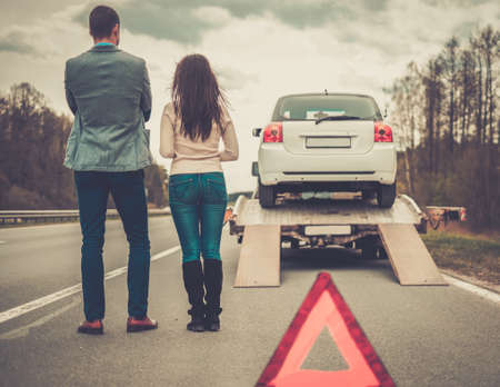 Foto per Couple near tow-truck picking up broken car - Immagine Royalty Free
