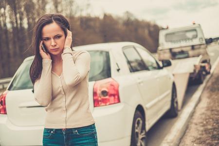 Foto de Woman calling while tow truck picking up her car - Imagen libre de derechos