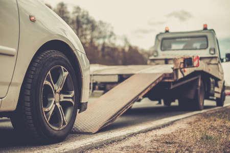 Foto de Loading broken car on a tow truck on a roadside - Imagen libre de derechos