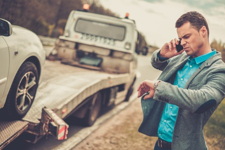 Photo for Man calling while tow truck picking up his broken car - Royalty Free Image