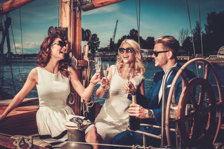 Foto de Stylish wealthy friends having fun on a luxury yacht - Imagen libre de derechos