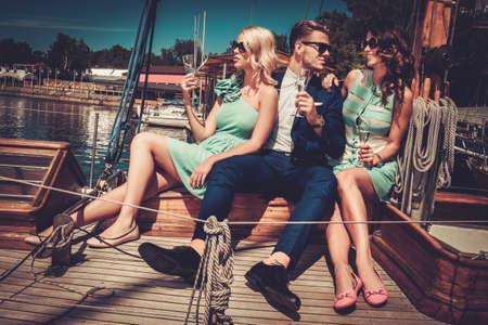 Photo pour Stylish wealthy friends having fun on a luxury yacht - image libre de droit