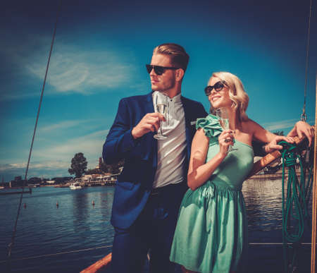 Photo pour Stylish wealthy couple on a luxury yacht - image libre de droit