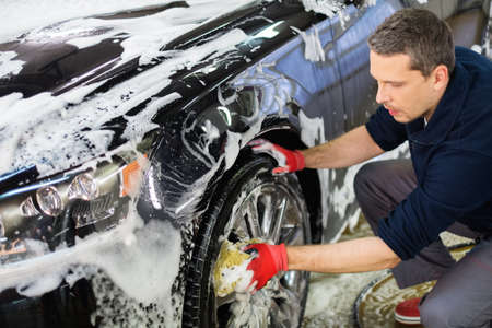 Photo pour Man worker washing car's alloy wheels on a car wash - image libre de droit