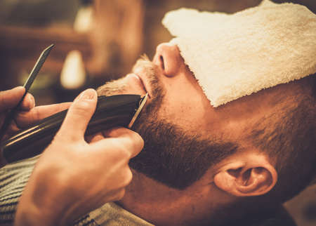 Photo pour Client during beard and moustache grooming in barber shop - image libre de droit
