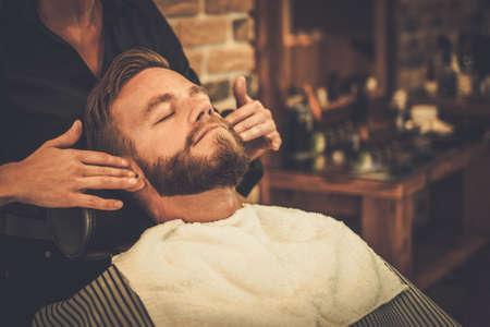 Photo pour Hairstylist applying after shaving lotion in barber shop - image libre de droit