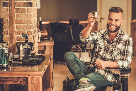 Photo pour Happy client in barber shop will glass of whiskey - image libre de droit