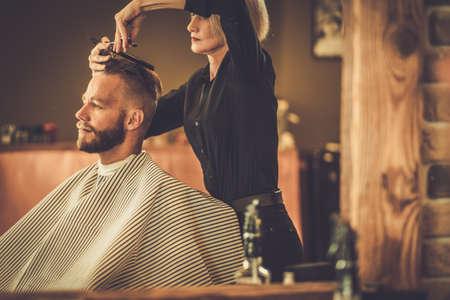 Photo pour Client visiting hairstylist in barber shop - image libre de droit
