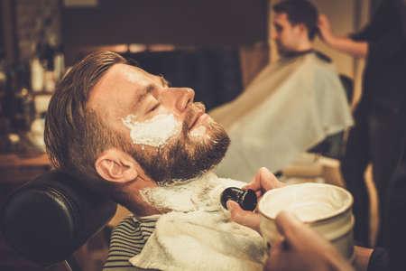 Foto de Client during beard shaving in barber shop - Imagen libre de derechos