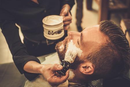 Photo pour Client during beard shaving in barber shop - image libre de droit