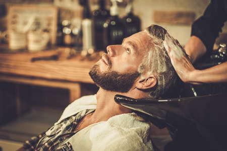 Photo pour Hairstylist washing client's hair in barber shop - image libre de droit