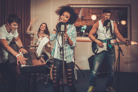 Photo for Multiracial music band performing in a recording studio - Royalty Free Image
