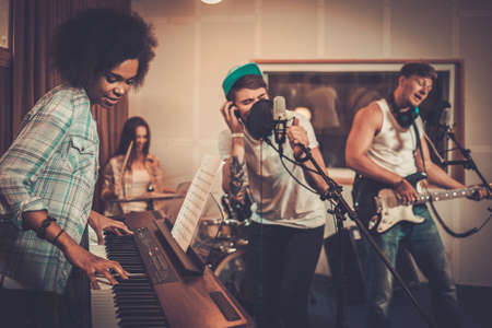 Photo pour Multiracial music band performing in a recording studio - image libre de droit