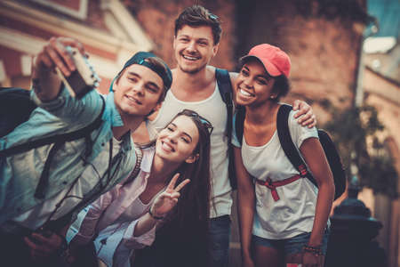 Foto de Multiracial friends tourists making selfie in an old city - Imagen libre de derechos