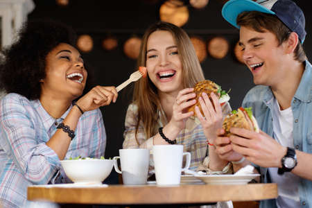 Photo pour Cheerful multiracial friends eating in a cafe - image libre de droit