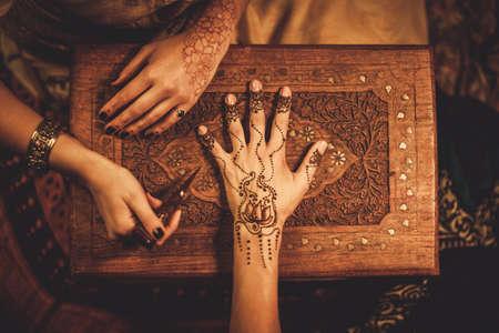 Photo pour Drawing process of henna menhdi ornament on woman's hand - image libre de droit