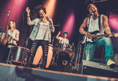 Photo for Multiracial music band performing on a stage - Royalty Free Image
