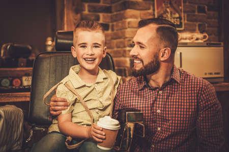 Foto de Stylish little boy and his father in a barber shop - Imagen libre de derechos