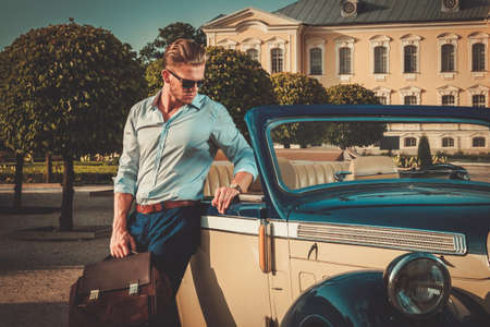Foto de Confident wealthy young man with briefcase near classic convertible - Imagen libre de derechos